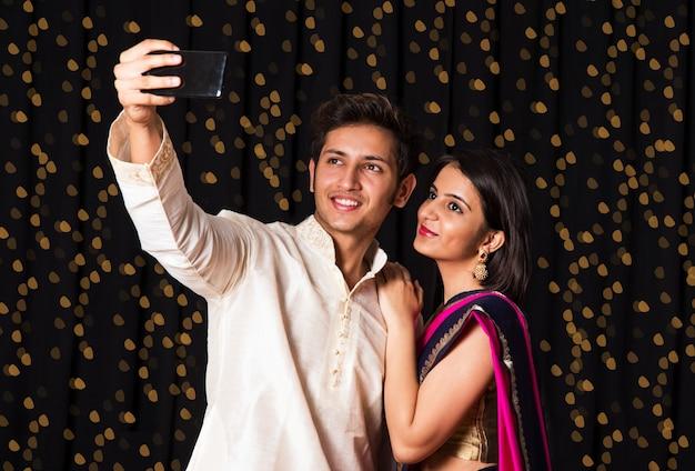 Giovani coppie indiane che prendono un autoritratto o un selfie utilizzando lo smartphone nel festival di diwali su sfondo nero con bokeh di serie di luci