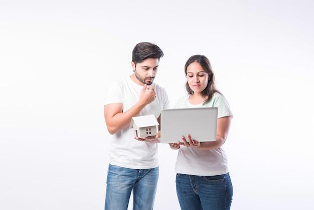 Coppia giovane famiglia indiana che sceglie una nuova casa online, cerca immobili da acquistare o affittare, casa in vendita sullo schermo del computer, in piedi su sfondo bianco