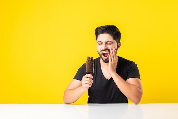 Giovane indiano che mangia il gelato nel cono e ha mal di denti a causa della cavità, seduto a tavola su sfondo giallo o bianco