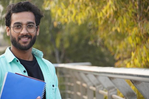 Giovane studente indiano con il primo piano del libro