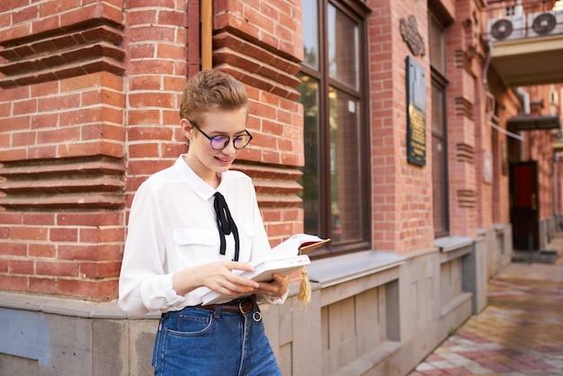 Donna indignata con libro vicino edificio in mattoni di stile retrò istituto di istruzione