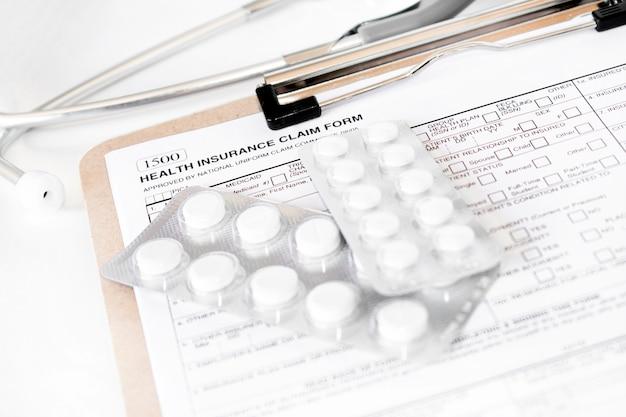 . polizza di assicurazione sanitaria individuale con stetoscopio e pillole bianche