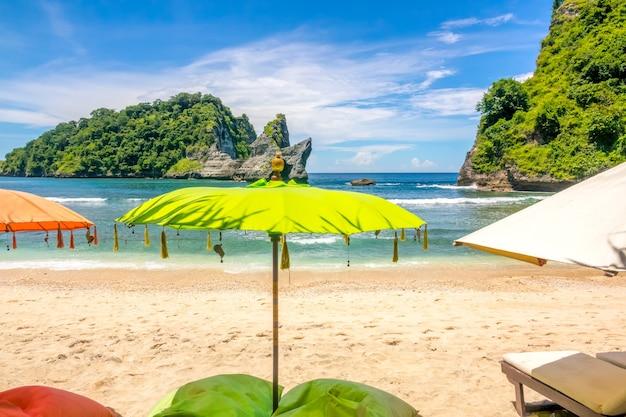Indonesia. una piccola spiaggia sabbiosa su un'isola tropicale. ombrelloni e lettini in primo piano. oceano e isolotto roccioso sullo sfondo. nessuno