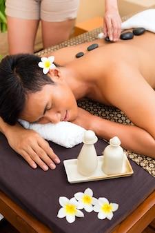 Uomo asiatico indonesiano nel centro termale di giorno di bellezza di benessere che ha massaggio o trattamento con pietre calde, guardando rilassato
