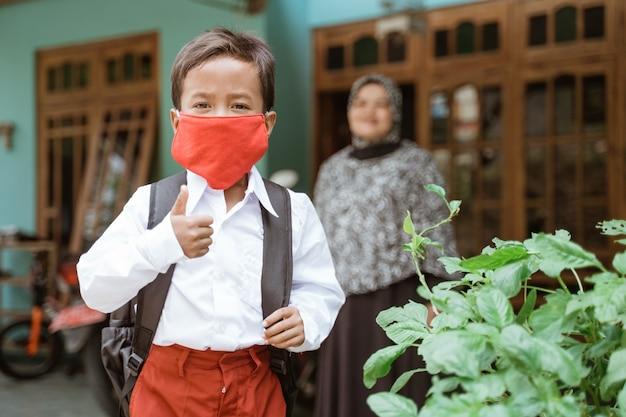 Studente primario asiatico indonesiano che indossa una maschera prima di andare a scuola