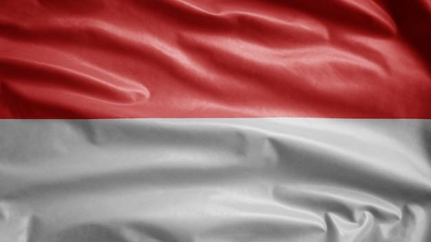 Bandiera indonesiana che ondeggia nel vento. close up indonesia banner che soffia, seta morbida e liscia
