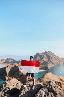 Uomo indonesiano che tiene la bandiera dell'indonesia a labuan bajo