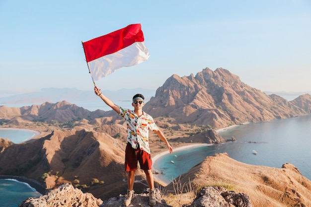 Uomo indonesiano che sventola la bandiera dell'indonesia a labuan bajo con orgoglio
