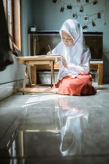Studentessa indonesiana che studia i compiti durante la lezione online a casa