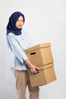 Donna indonesiana in hijab che si lamenta sollevando due pesanti scatole