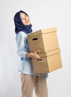 Donna indonesiana in hijab che solleva due scatole pesanti