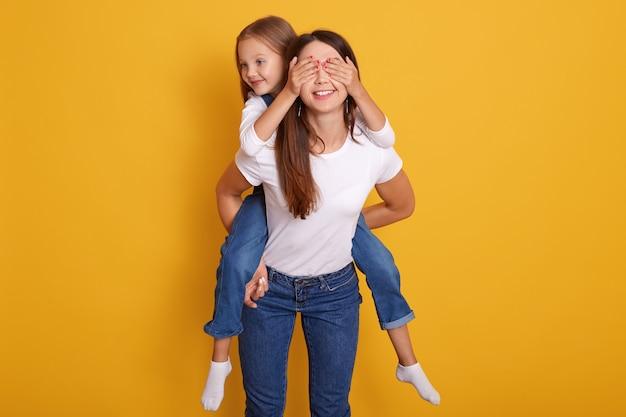 Colpo di indooor della madre felice che trasporta sulle spalle la figlia mentre bambino sveglio che la chiude occhi