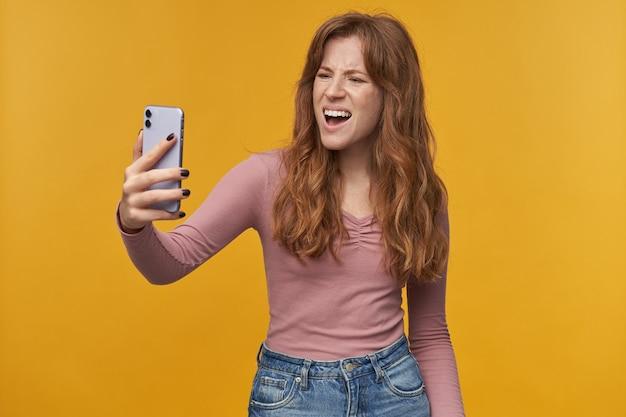 Ritratto indoor di una giovane donna allo zenzero con capelli mossi e lentiggini, litiga con il suo ragazzo mentre fa una videochat con lui