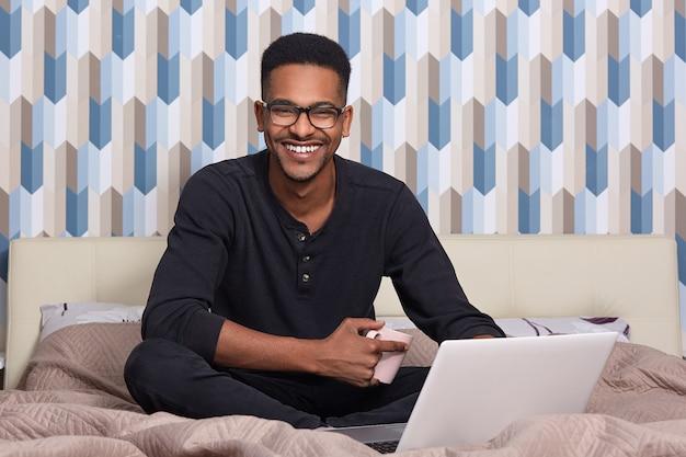 Ritratto dell'interno di giovane uomo di colore bello che si siede sul letto con la tazza di caffè
