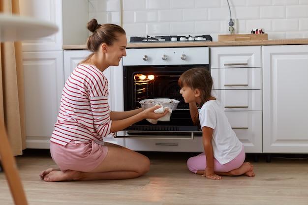 Colpo di profilo dell'interno di sorridere che prende la cottura dal forno, sua figlia in piedi vicino e annusando deliziosi dolci, bambino che aiuta la madre in cucina, famiglia in posa a casa mentre è seduta sul pavimento.
