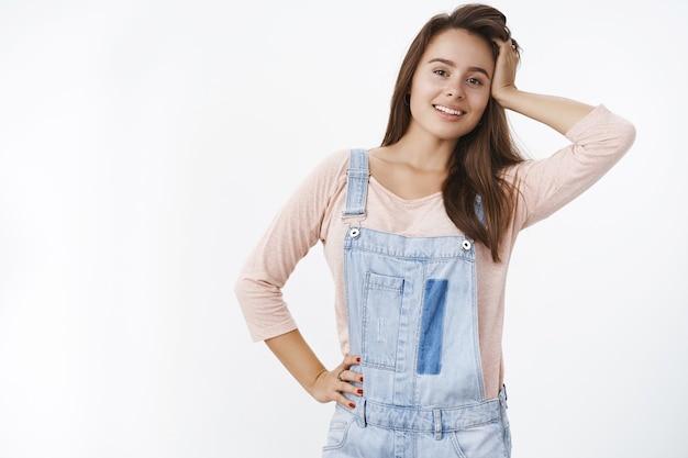 Colpo al coperto di un'attraente donna bruna in salopette di jeans che gioca con i capelli e tiene la mano sul fianco mentre sorride ampiamente davanti facendo sguardi carini, flirtando sul muro grigio.