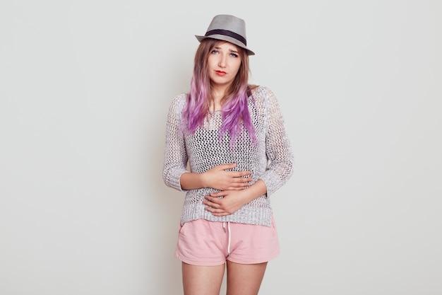 Colpo al coperto di una giovane ragazza attraente con i capelli viola, che indossa un cappello, che soffre di mal di stomaco o dolori mestruali, ha problemi di salute, isolato su sfondo grigio.