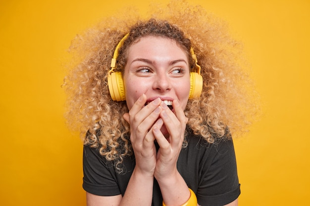 Colpo al coperto di felice donna dai capelli ricci ridacchia e copre la bocca con le mani guarda lontano indossa le cuffie wireless si diverte ad ascoltare musica