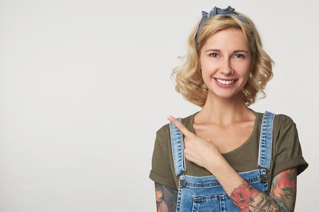 Ripresa in interni di una donna felice con un sorriso piacevole, punta con un dito con spazio per la copia su grigio