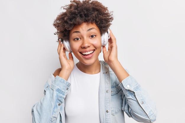 Colpo al coperto di una ragazza millenaria spensierata positiva con i capelli ricci gode di buone melodie in cuffia ascolta podcast audio musica preferita sorride felicemente indossa abiti eleganti isolati su muro bianco