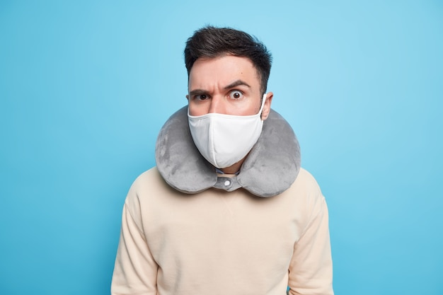 Il tiro al coperto di un uomo serio e attento indossa una maschera protettiva contro il cuscino del collo gonfiato dal coronavirus per dormire comodamente durante il viaggio durante il trasporto alza il sopracciglio con attenzione,