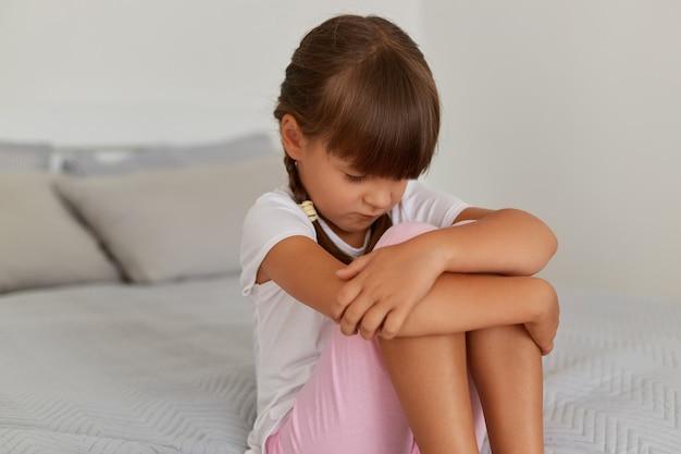Colpo al coperto di una ragazzina sconvolta che indossa una maglietta bianca e pantaloncini rosa, seduta sul letto con la testa in giù, sembra offesa, il bambino è punito dai suoi genitori per cattivo comportamento.