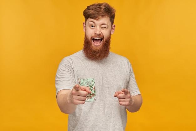 Colpo al coperto di un giovane bel maschio allo zenzero con una grande barba, che indica con entrambe le mani davanti, sorride e fa l'occhiolino