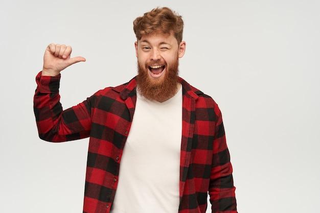 Colpo al coperto di un giovane uomo felice con una grande barba e capelli rossi, indossa una camicia alla moda, indica se stesso con il pollice