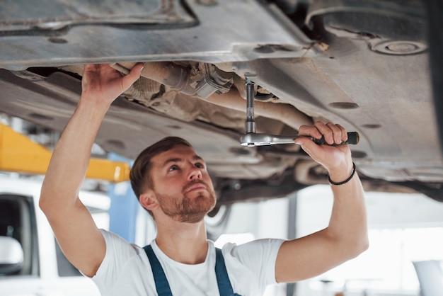 Al chiuso nel suo garage. l'impiegato con l'uniforme di colore blu lavora nel salone dell'automobile.