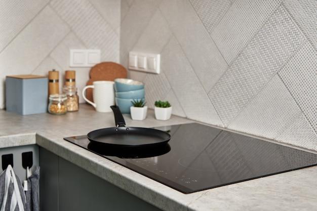 Fornello a induzione con padella su di esso moderno elettrodomestico da cucina