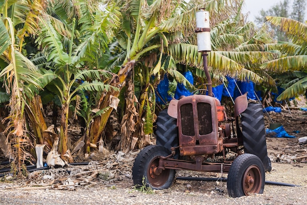 Scena agricola industriale di vecchio trattore arrugginito e polveroso abbandonato