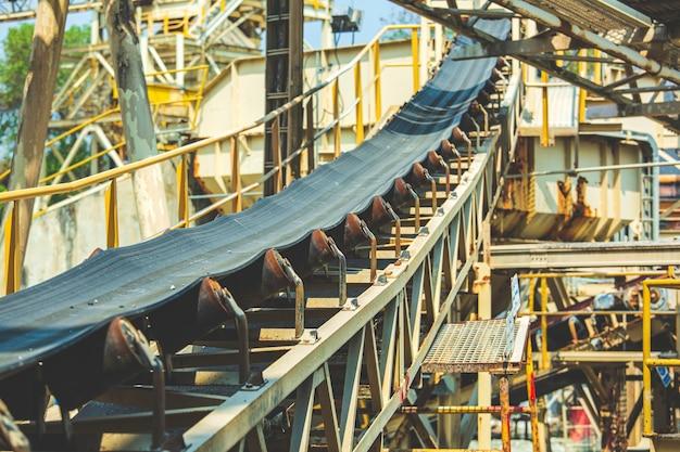 Nastro trasportatore industriale che sposta le materie prime dall'oro della miniera