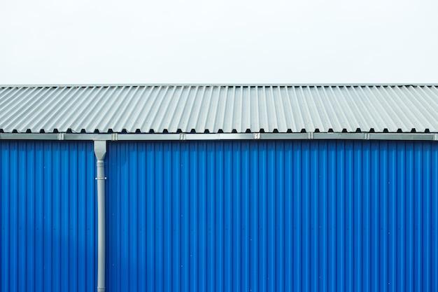 Edificio industriale facciata in lamiera blu, sfondo astratto.