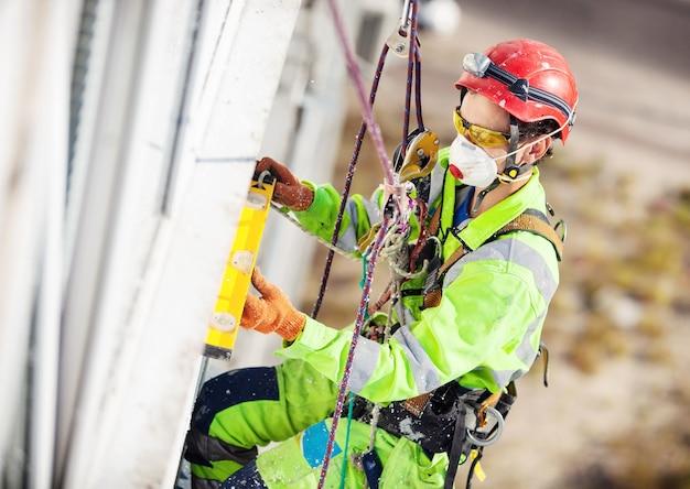 Scalatore industriale che misura con tubo di livello durante i lavori di svernamento
