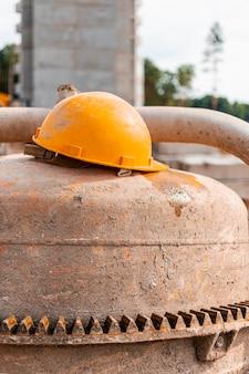 Una betoniera industriale in un cantiere con il casco di un lavoratore arancione sdraiato su di esso. preparazione concreta.