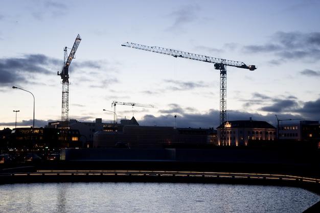 Gru edili industriali e sagome di edifici sopra il sole all'alba.