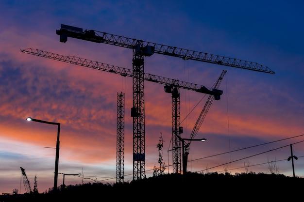 Gru industriali che costruiscono lo sfondo del tramonto di oslo