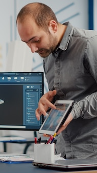 Progettista industriale che tiene tablet discutendo con l'ingegnere donna mentre lavora nella progettazione del programma cad...