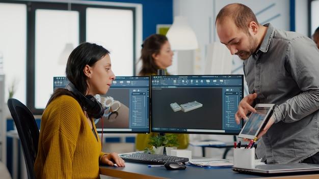 Designer industriale con tablet che discute con un ingegnere donna mentre lavora in un programma cad cad