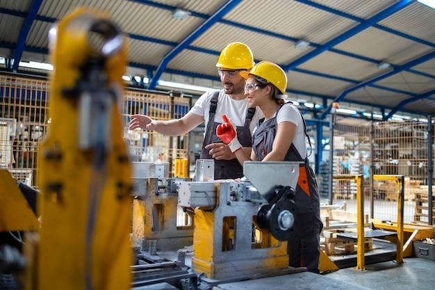 Dipendenti industriali che lavorano insieme nella linea di produzione in fabbrica.