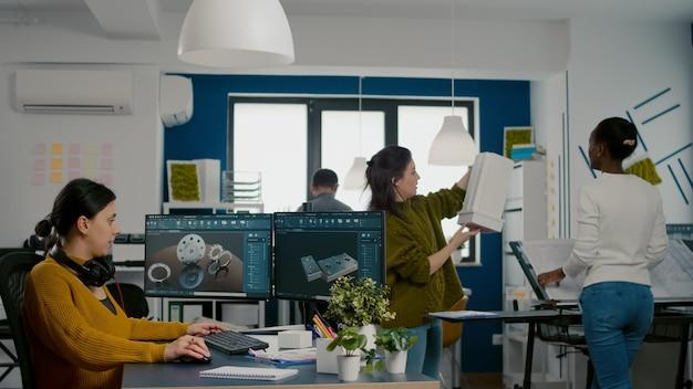 Ingegnere industriale che indossa le cuffie che lavora al pc con due monitor