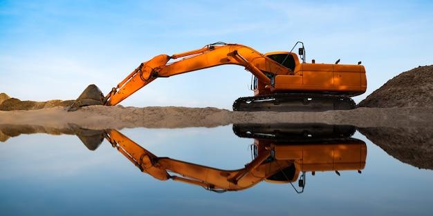 L'escavatore industriale sta scavando la sabbia in riva al fiume sul blu