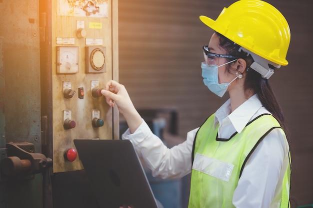 La donna degli ingegneri di manutenzione della fabbrica industriale ispeziona il sistema di protezione del relè dei macchinari e che tiene il taccuino con lo spazio della copia. concetto di industria, manutenzione, ingegneria e costruzione.