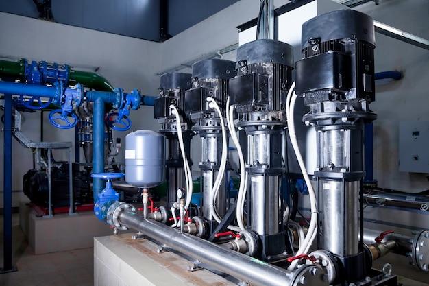 Interno industriale della pompa dell'acqua, valvole, manometri, motori all'interno della sala macchine. valvola e pompe in un locale industriale. condutture e pompe moderne e moderne urbane, sistemi di controllo automatici