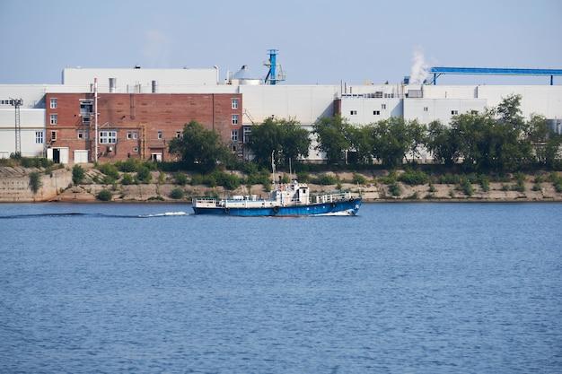 Paesaggio industriale con una fabbrica sulle rive del fiume, lungo la quale galleggia una motonave
