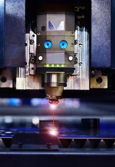Macchina taglio laser industriale durante il taglio della lamiera con la luce scintillante