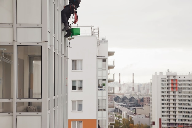 L'alpinista industriale pende dall'edificio residenziale mentre lava i vetri della facciata esterna. l'addetto alla fune è appeso al muro della casa. concetto di opere urbane. copia spazio