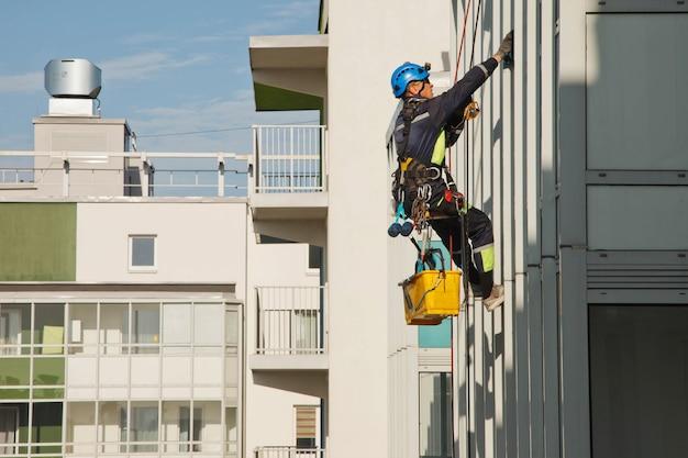 L'alpinista industriale pende dall'edificio residenziale mentre lava i vetri della facciata esterna