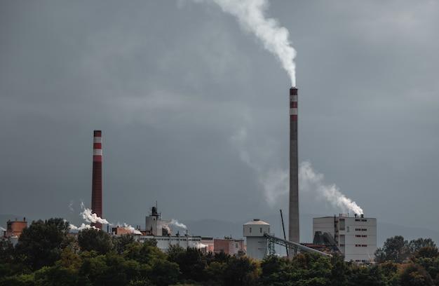 Fumo industriale dal camino sul cielo nuvoloso