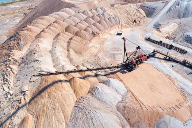 Uno spargitore industriale nel processo di lavoro. il processo di versamento delle pile di rocce
